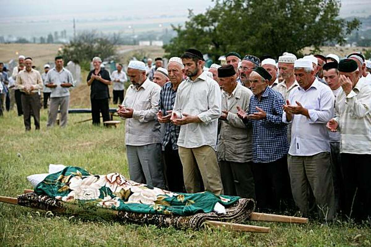 People pray at the burial of slaim rights activist Natalya Estemirova at a cemetery in Koshkeldy, 70 km (44 miles) east of Grozny, Chechnya, Thursday, July 16, 2009. Weeping mourners escorted the body of Natalya Estemirova through Chechnya's capital on Thursday, honoring the activist whose brazen kidnapping and execution-style killing shocked Russia's beleaguered human rights community and prompted international outrage. (AP Photo/Musa Sadulayev)