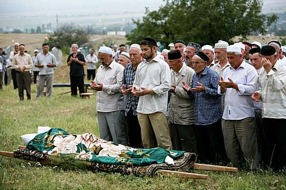 People pray at the burial of slaim rights activist Natalya Estemirova at a cemetery  in Koshkeldy, 70 km (44 miles) east of Grozny, Chechnya, Thursday, July 16, 2009. Weeping mourners escorted the body of Natalya Estemirova through Chechnya's capital on Thursday, honoring the activist whose brazen kidnapping and execution-style killing shocked Russia's beleaguered human rights community and prompted international outrage. (AP Photo/Musa Sadulayev) Photo: Musa Sadulayev, AP