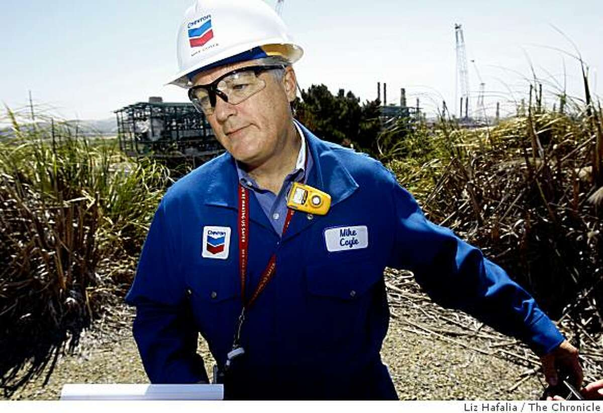 General manager of Chevron Richmond refinery Mike Coyle talks about the demobilization of the oil refinery expansion (behind) in Richmond, Calif., as workers demobilize the Praxair hydrogen plant on Wednesday, July 8, 2009.