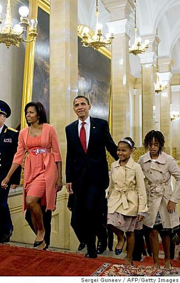 """US President Barack Obama, his wife Michelle and their daughters Sasha and Malia walk through the Kremlin in Moscow on July 6, 2009. US President Barack Obama faces a delicate balancing act on human rights as he visits Moscow in a bid to """"reset"""" strained relations and win Russia's support on a range of pressing security issues.       AFP PHOTO / RIA NOVOSTI / SERGEI GUNEEV (Photo credit should read SERGEI GUNEEV/AFP/Getty Images) Photo: Sergei Guneev, AFP/Getty Images"""