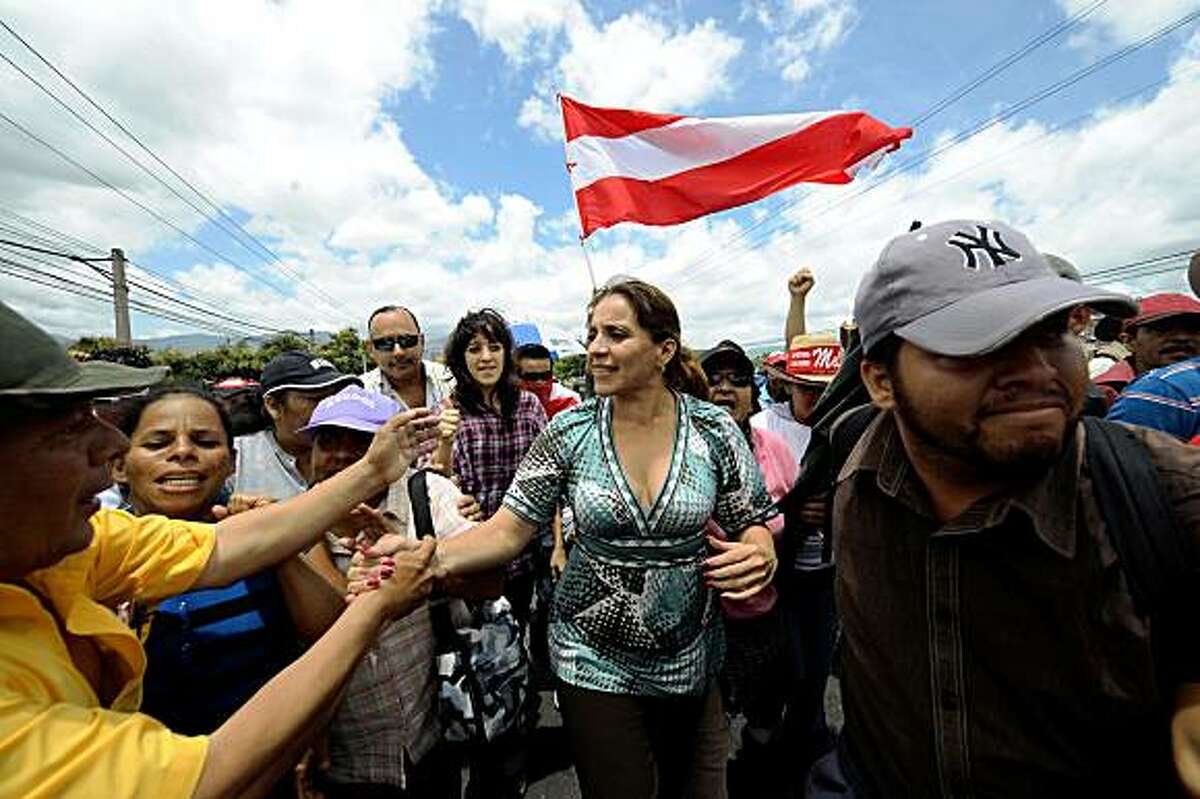 The wife of Honduran ousted President Manuel Zelaya, Xiomara Castro de Zelaya (C), joins supporters of her husband protesting in Tegucigalpa on July 18, 2009. Honduras's military was on alert Saturday for a possible return attempt by Zelaya, as talks between his aides and the country's de facto government were held in Costa Rica. Tensions were ratcheted up after days of protests by thousands of Zelaya supporters who blocked roads around the capital. AFP PHOTO/Orlando SIERRA (Photo credit should read ORLANDO SIERRA/AFP/Getty Images)