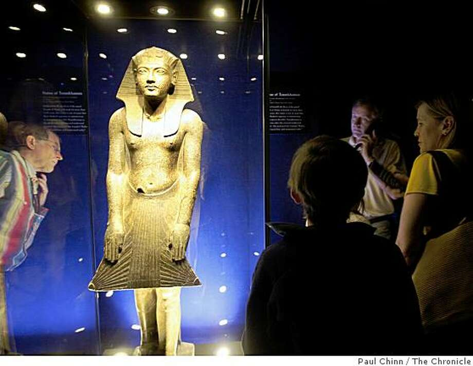 Visitors in the first group allowed in study a statue of Tutankhamun in the King Tut exhibit after it opened to the public at the de Young Museum in San Francisco, Calif., on Saturday, June 27, 2009. Photo: Paul Chinn, The Chronicle