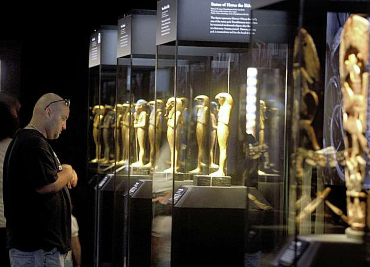 A first-day visitor views a row of statues displayed in the King Tut exhibit at the de Young Museum in San Francisco, Calif., on Saturday, June 27, 2009.