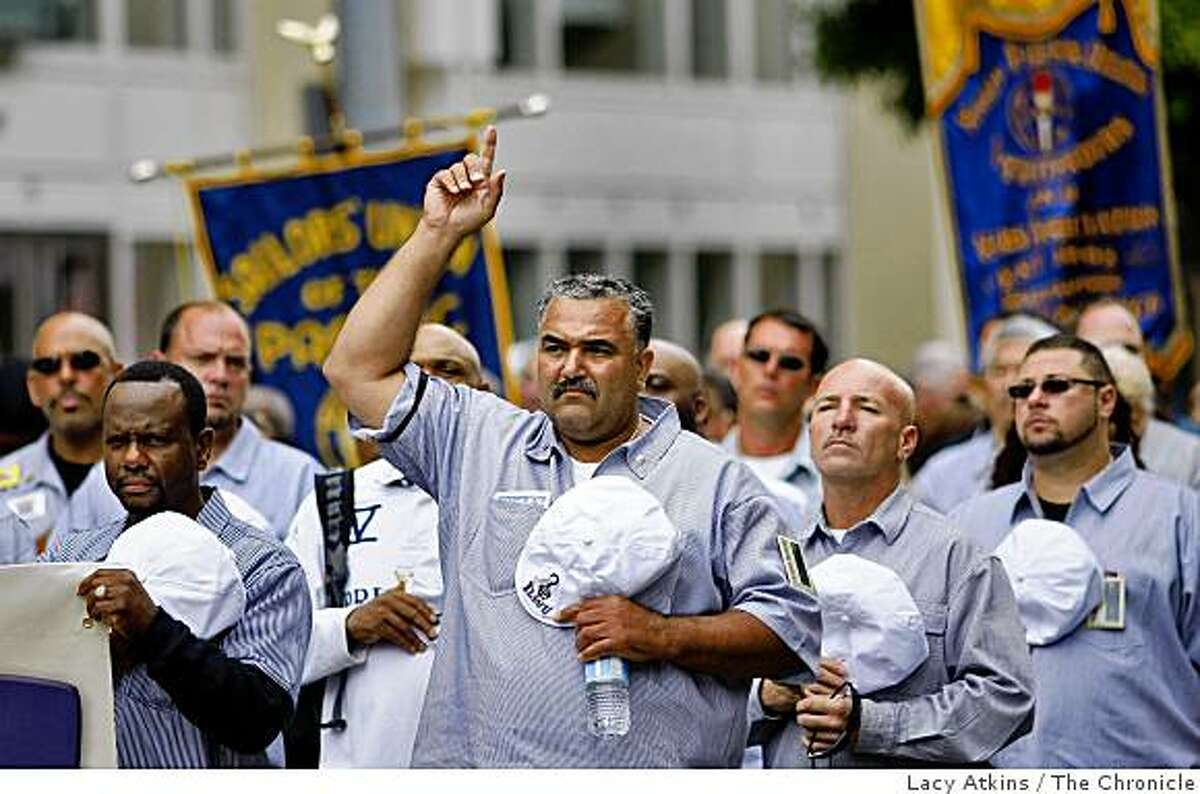 Henry Pellom III raises his arm as well as takes his hat off as they group passes the Union Memorial on the cornor of Stewart and Mission to pay homage to those who were killed 75 years ago in the General Strike, Sunday July 5, 2009, in San Francisco, Calif.