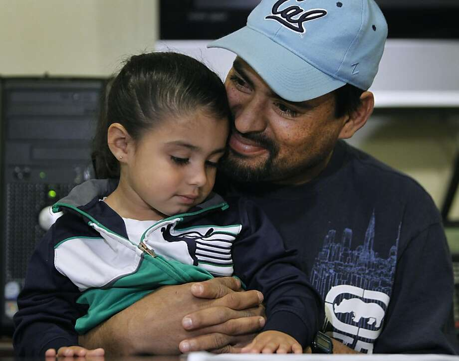 Jesus Navarro hugs his 3-year-old daughter Karin Jacquelin while describing his need for a kidney transplant in Berkeley, Calif. on Thursday, Feb. 9, 2012. However, Navarro's immigration status may create complications in his receiving publicly-assisted post-op medical care. Photo: Paul Chinn, The Chronicle