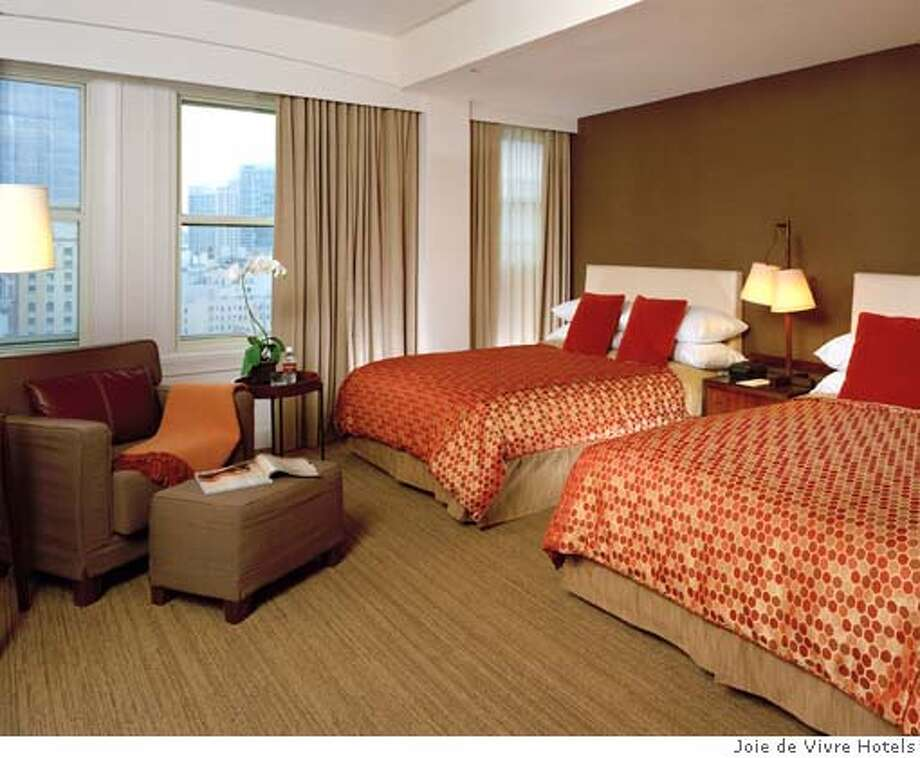 TRAVEL UNDER COVERS -- A double room at the Hotel Adagio, which has tall windows overlooking the Union Square neighborhood and harvest colors. Photo courtesy Joie de Vivre Hotels Photo: HO