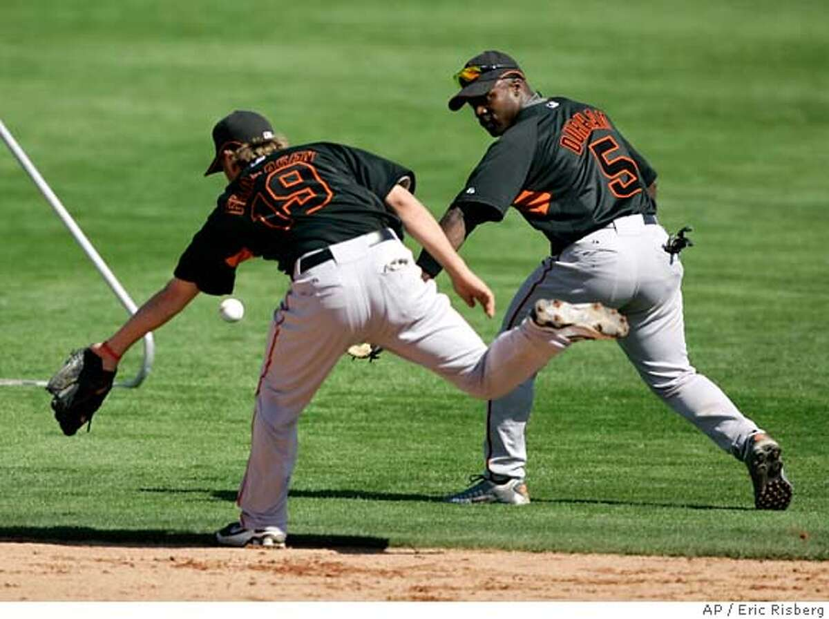 San Francisco Giants second basemen Kevin Frandsen, left, and Ray Durham, right, chase after a ground ball during their spring training baseball workout in Scottsdale, Ariz., Saturday, Feb. 23, 2008. (AP Photo/Eric Risberg) EFE OUT