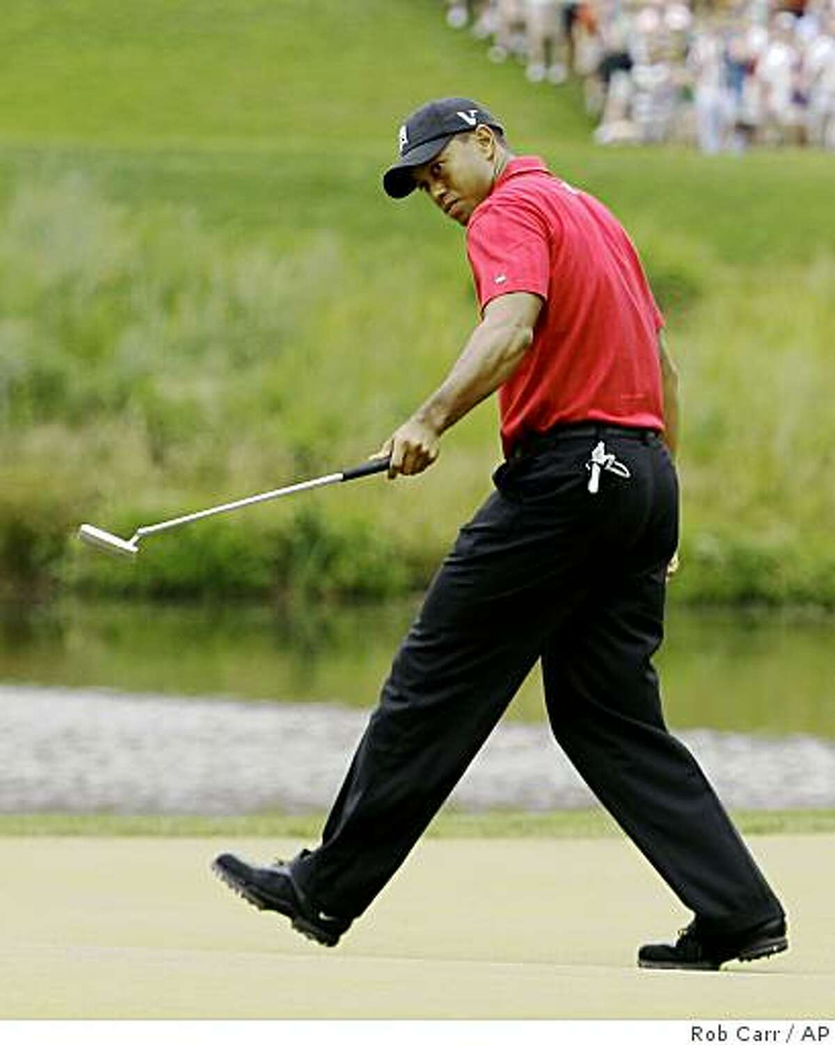 Tiger Woods watches his birdie putt roll into the hole on the 10th hole during the final round of the AT&T National golf tournament at Congressional Country Club, Sunday, July 5, 2009, in Bethesda, Md. (AP Photo/Rob Carr)