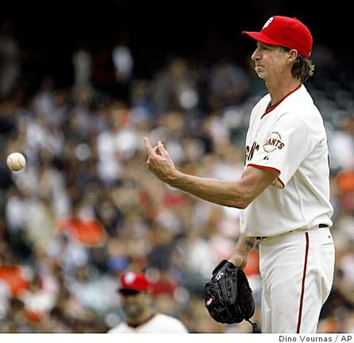 San Francisco Giants pitcher Randy Johnson tosses the ball back to the catcher after a run scored because of his throwing error against the Houston Astros in the fourth inning of a baseball game, Sunday, July 5, 2009 in San Francisco. (AP Photo/Dino Vournas)