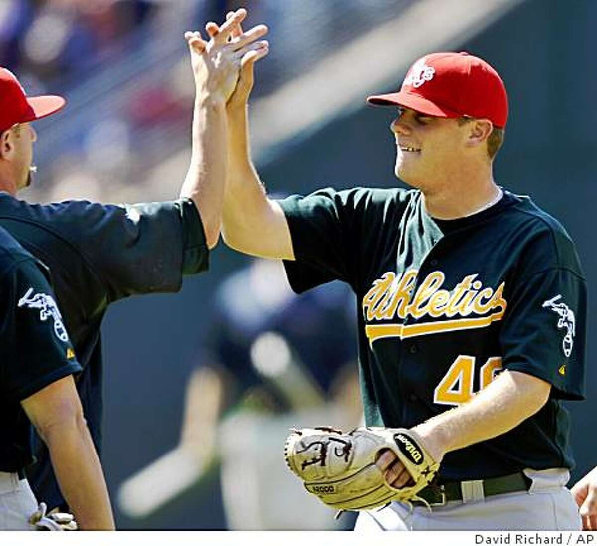 Oakland Athletics pitcher Andrew Bailey is congratulated by teammates after recording his ninth save in a win over the Cleveland Indians in a baseball game on Sunday, July 5, 2009, at Progressive Field in Cleveland, Ohio. (AP Photo/David Richard)