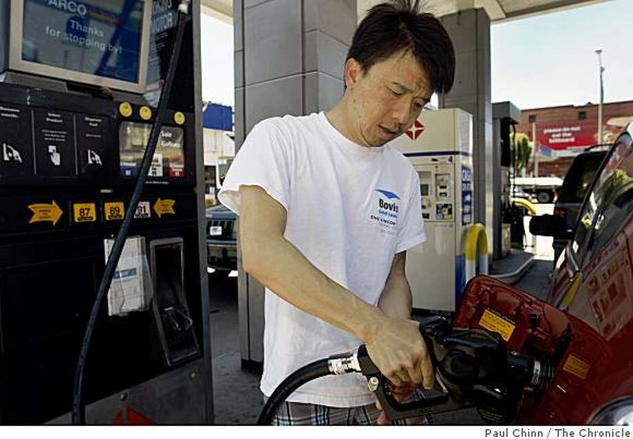 "Evans Fung fills his hybrid's gas tank at the Arco station at Fell and Divisadero streets in San Francisco, Calif., on Tuesday, July 14, 2009. At $2.75 a gallon, the station is among the lowest in town. ""I always gas up here,"" Fung said. ""It's consistently the cheapest around"". Photo: Paul Chinn, The Chronicle"