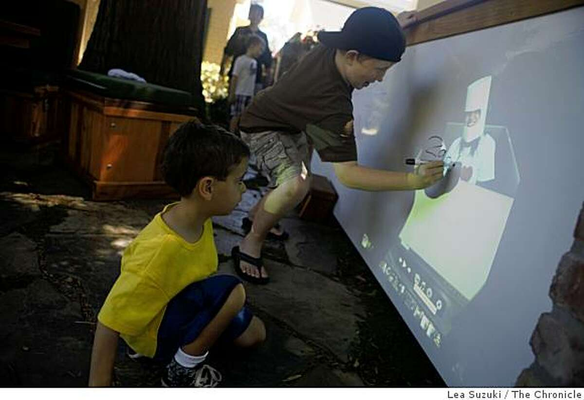 Zach Drevno, 9, writes his name on a image projected onto a whiteboard while (name TK) watches during Camp Yale on Thursday June 18, 2009 in Menlo Park, Calif. The projector is stowed under the seat of a bench and continually ran a slideshow projected onto the whiteboard. 3 large whiteboards create a fence which the children can draw on in Lanza's front yard.