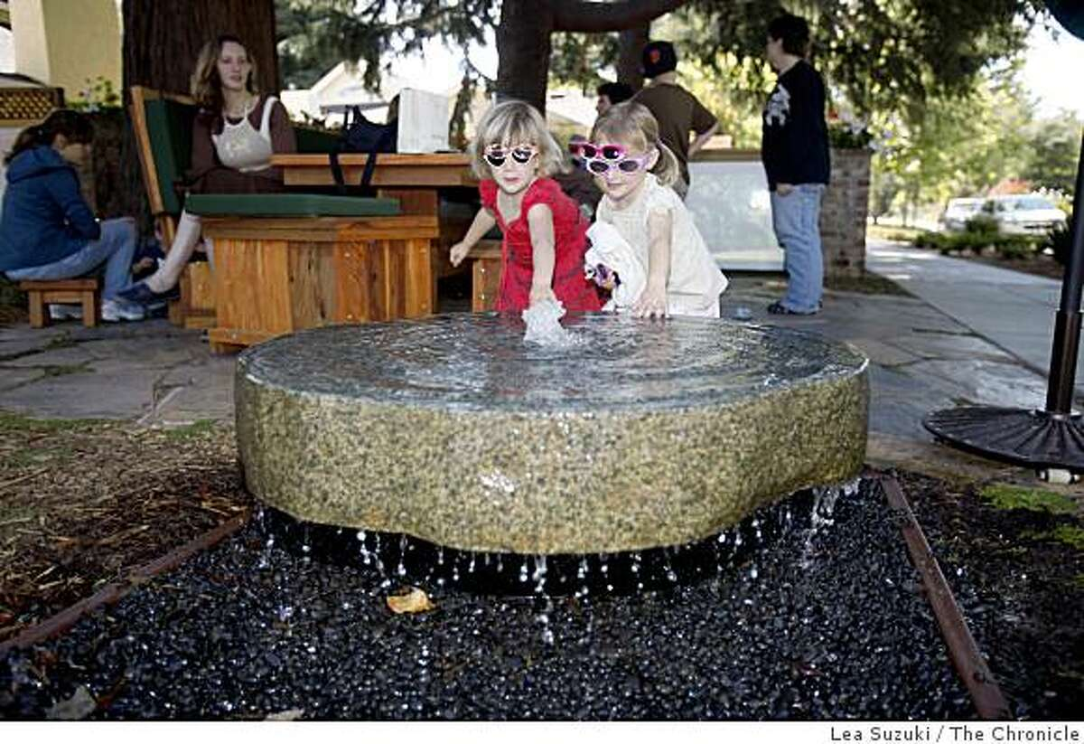Julia Pletcher, 3, (l to r) and Tatum Olesen, 3, touch the water in a fountain in the front yard of Mike Lanza's home on Thursday June 18, 2009 in Menlo Park, Calif.