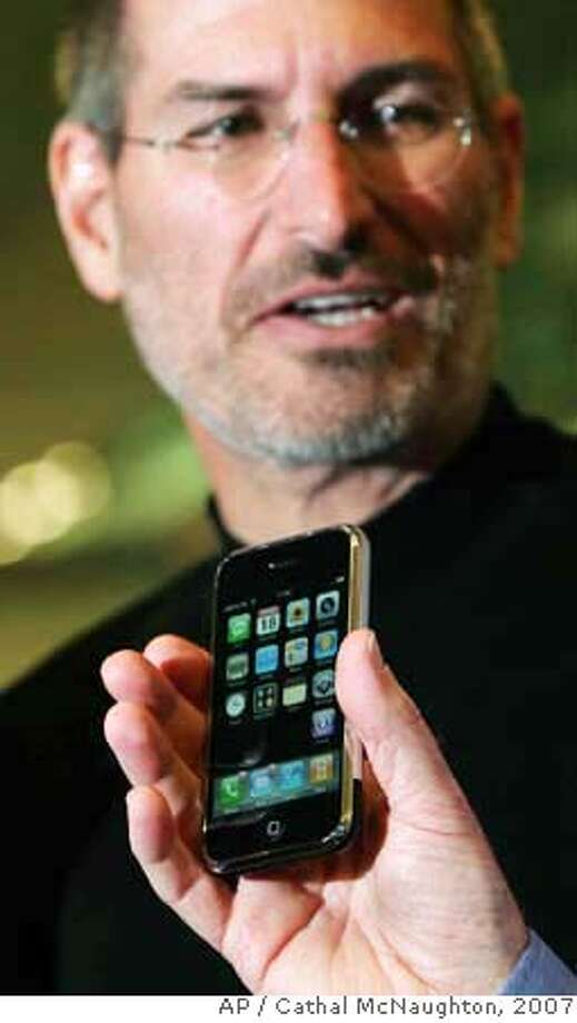 ###Live Caption:Apple CEO Steve Jobs is seen at the Apple store on Regent Street for the announcement of its long-awaited iPhone, as an unidentified person holds up the device in the foreground, London, Sept. 18, 2007. Apple Inc.'s iPhone will go on sale in Britain on Nov. 9 and have the O2 network as its exclusive carrier, Apple CEO Steve Jobs said Tuesday. The 8-gigabyte model will sell for 269 pounds (US$536, euro 386). (AP Photo/PA, Cathal McNaughton) ** UNITED KINGDOM OUT NO SALES NO ARCHIVE ** Ran on: 09-19-2007 Apple CEO Steve Jobs appears at an Apple store in London to announce plans to sell the iPhone in Britain through carrier O2, without the discounts typical of even high-end phones in Europe.###Caption History:Apple CEO Steve Jobs is seen at the Apple store on Regent Street for the announcement of its long-awaited iPhone, as an unidentified person holds up the device in the foreground, London, Sept. 18, 2007. Apple Inc.'s iPhone will go on sale in Britain on Nov. 9 and have the O2 network as its exclusive carrier, Apple CEO Steve Jobs said Tuesday. The 8-gigabyte model will sell for 269 pounds (US$536, euro 386). (AP Photo/PA, Cathal McNaughton) ** UNITED KINGDOM OUT NO SALES NO ARCHIVE **  Ran on: 09-19-2007  Apple CEO Steve Jobs appears at an Apple store in London to announce plans to sell the iPhone in Britain through carrier O2, without the discounts typical of even high-end phones in Europe.###Notes:###Special Instructions:UNITED KINGDOM OUT NO SALES NO ARCHIVE - PHOTOGRAPH CAN NOT BE STORED OR USED FOR MORE THAN 14 DAYS AFTER THE DAY OF TRANSMISSION Photo: CATHAL MCNAUGHTON