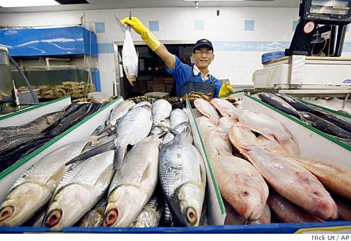 In a Thursday, June 4, 2009 photo, Hoang Van Nguyen holds milkfish at Thuan Phat market in Westminster, Calif. State and county authorities are inspecting Asian markets in Southern California to try to weed out the sale of white croaker, which has been contaminated by chemicals released into the Pacific Ocean from the 1950s to the 1970s. (AP Photo/Nick Ut)