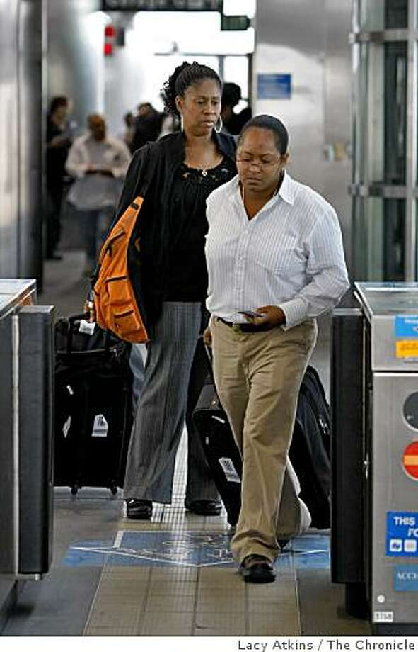 Travelers Darice Hanna (right) and Arletha Simon walk through the gate to get on the  BART train from SFO, Thursday  May 28, 2009, in San Francisco, Calif. Photo: Lacy Atkins, The Chronicle