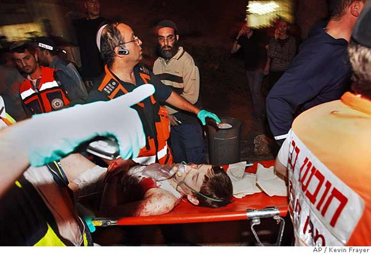 Medics evacuate a wounded Israeli from the site of a shooting attack in Jerusalem, Thursday, March 6, 2008. Two gunmen infiltrated a rabbinical seminary at the entrance of Jerusalem and opened fire after nightfall Thursday, killing at least seven, police and rescue workers said. (AP Photo/Kevin Frayer)