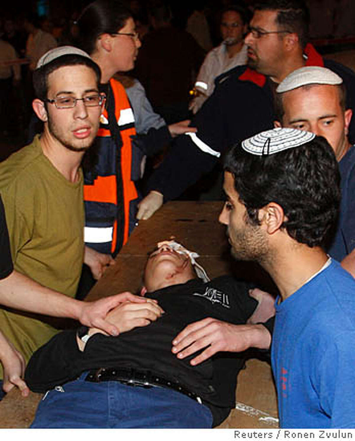 Jewish religious school students evacuate a fellow student after he was injured in a shooting attack in Jerusalem March 6, 2008. Two Palestinian gunmen opened fire in a Jewish religious school in Jerusalem on Thursday, killing at least six people, the Zaka emergency service said. The two gunmen were also killed in the assault at the Merkaz Harav seminary, Zaka said. But Israel Radio said one of the attackers may have escaped. REUTERS/Ronen Zvulun (JERUSALEM)