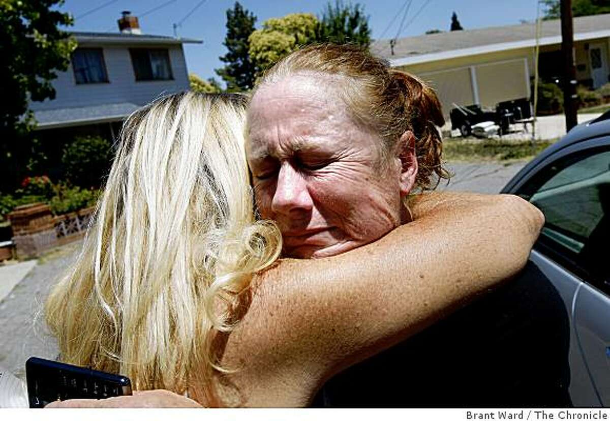 The victim's mother, Claudia Stevens, right, got a hug from a friend outside the home Claudia shared with Danielle. The son of former porn king Jim Mitchell was arrested for murder of Danielle Keller and the kidnapping of his one year old daughter.