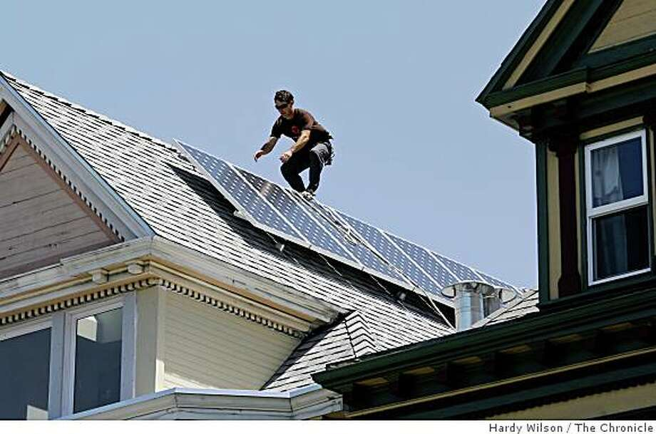Sungevity installation crew member Jeremiah Eanes scales a roof on a home at 1236 6th Avenue in San Francisco, Calif., after installing solar panels on Thursday, May 14, 2009. Sungevity, which is based out of Berkeley, Calif., installs solar panels on local homes and uses Microsoft Virtual Earth to calculate how to install them and what they will cost. Photo: Hardy Wilson, The Chronicle