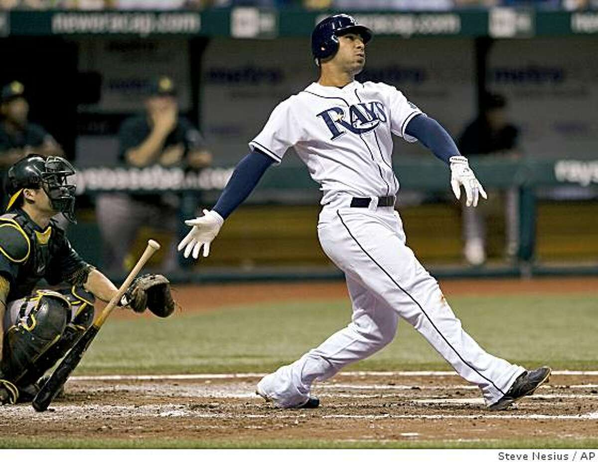 Tampa Bay Rays' Carlos Pena, right, and Oakland Athletics catcher Kurt Suzuki watch Pena's home run to right field off Oakland Athletics starter Vin Mazzaro during the fourth inning of a baseball game in St. Petersburg, Fla., Friday, July 10, 2009. (AP Photo/Steve Nesius)