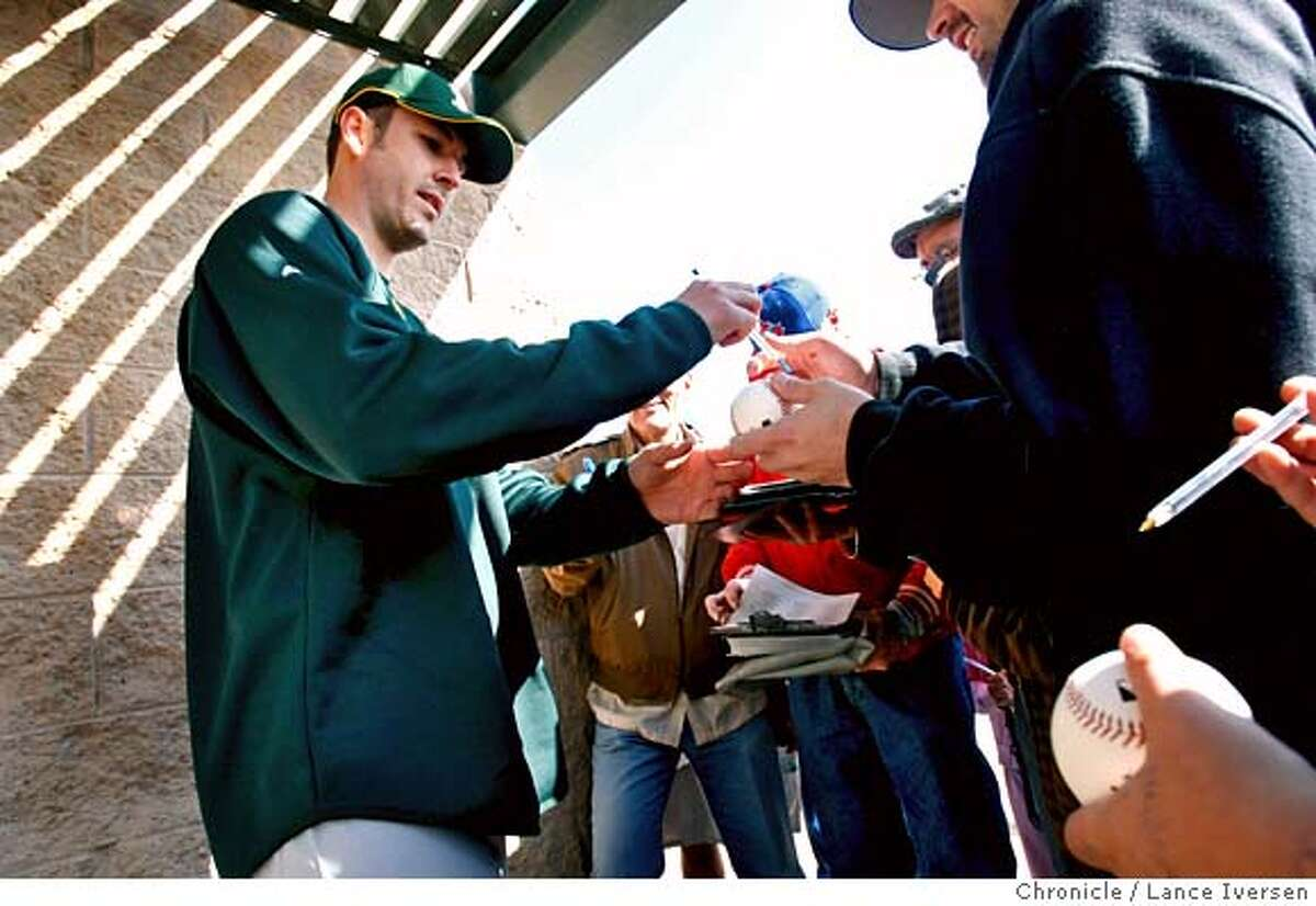 A's Justin Duchscherer signs autographs outside the clubhouse Saturday. Pitchers and catchers warm up on the infield at Papago Park, home of the Oakland Athletics for spring training in Phoenix, Saturday morning. By Lance Iversen/The San Francisco Chronicle MANDATORY CREDIT PHOTOG AND SAN FRANCISCO CHRONICLE/NO SALES MAGS OUT