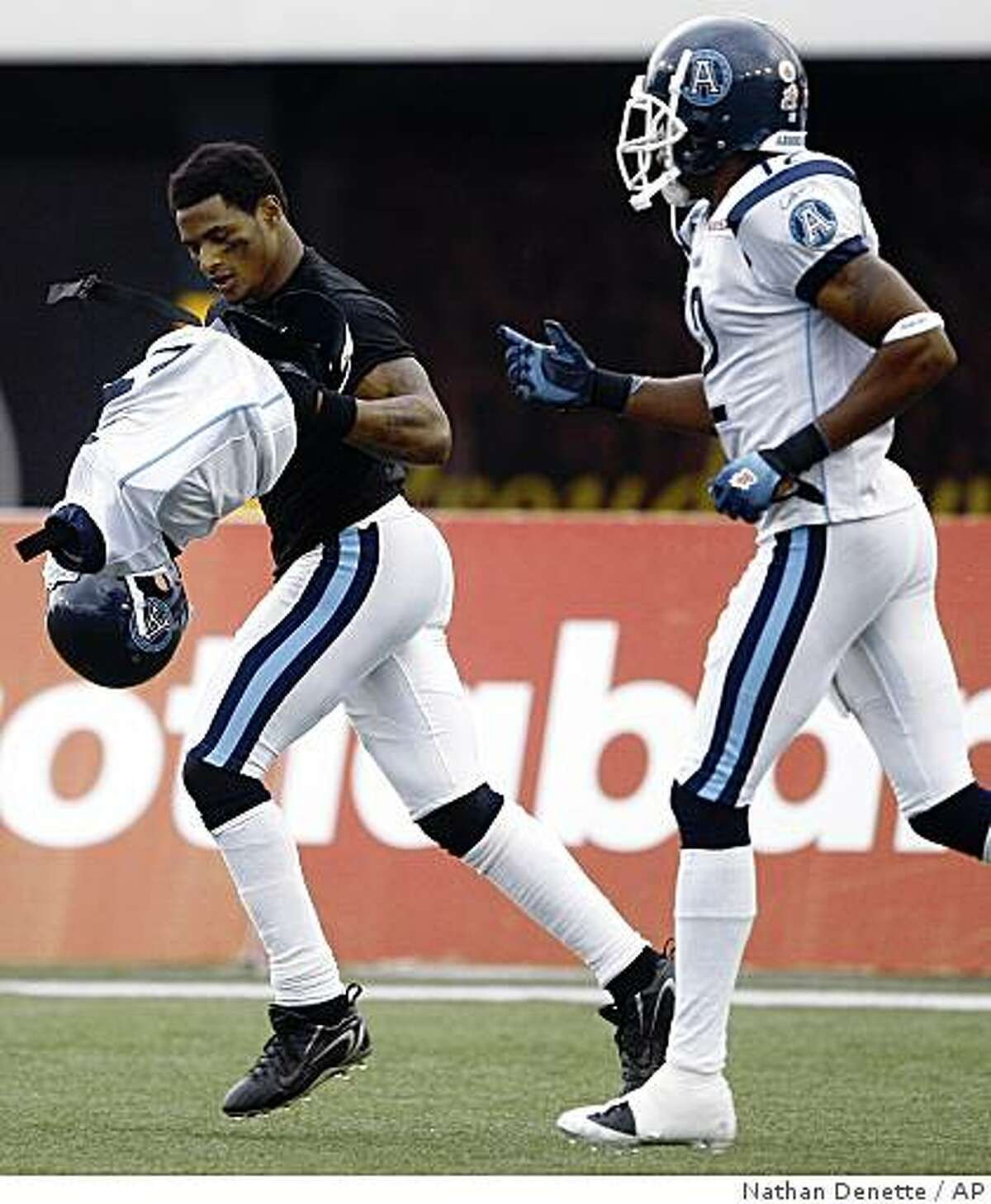 In this photo taken Wednesday, July 1, 2009, Toronto Argonauts Arland Bruce III, left, carries his football gear off the field as teammate Reggie McNeal, right, watches on after celebrating his touch down against the Hamilton Tiger-Cats during first half of a CFL football game in Hamilton, Ont. After scoring on a 21-yard pass from Kerry Joseph to put Toronto ahead 6-0, Bruce removed his helmet, shoulder pads and uniform top, then laid down in the end zone. Bruce said he was paying tribute to Michael Jackson. The CFL called it