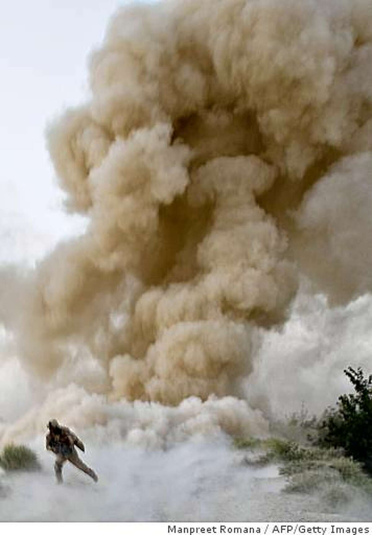 A US Marine of 2nd Marine Expeditionary Brigade runs to safety moments after an IED blast in Garmsir district of Helmand Province in Afghanistan on July 13, 2009. Two US Marine soldiers were killed when the explosion occured as they tried to clear a route into the Taliban heartland of southern Helmand province. About 4,000 US Marines are battling insurgents in a massive offensive launched in the south early this month to clear Taliban militants out of strongholds ahead of presidential and provincial council elections scheduled for August 20. AFP PHOTO/Manpreet ROMANA (Photo credit should read MANPREET ROMANA/AFP/Getty Images)