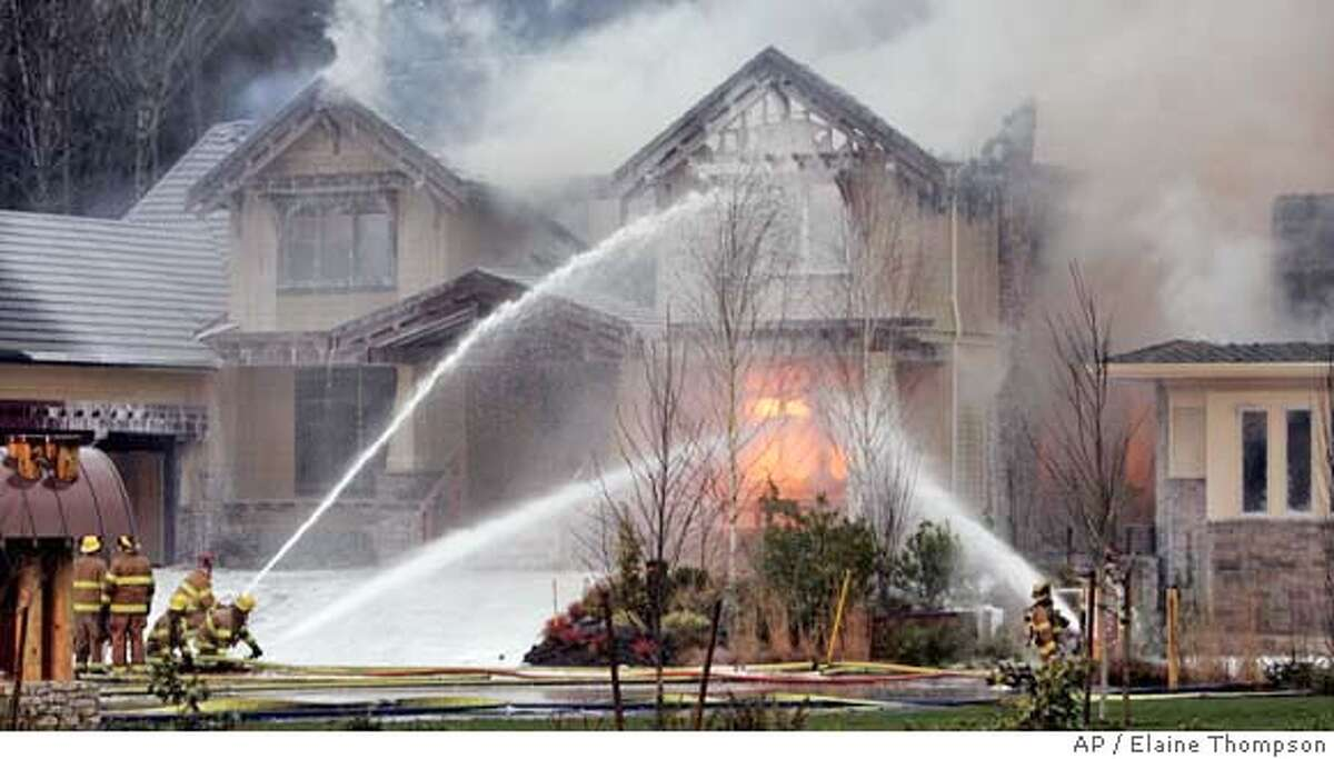 ###Live Caption:Firefighters spray a flaming house at the scene of where four multimillion dollar homes burned Monday, March 3, 2008, in Woodinville, Wash. Crews battled the fires early Monday in a suburb north of Seattle, and a sign with the initials of a radical environmental group was found at the scene, an official said. (AP Photo/Elaine Thompson)###Caption History:Firefighters spray a flaming house at the scene of where four multimillion dollar homes burned Monday, March 3, 2008, in Woodinville, Wash. Crews battled the fires early Monday in a suburb north of Seattle, and a sign with the initials of a radical environmental group was found at the scene, an official said. (AP Photo/Elaine Thompson)###Notes:###Special Instructions: