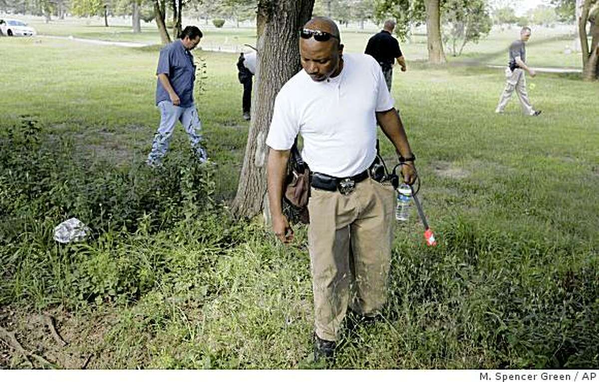 Investigators comb the grounds of the now-closed Burr Oak Cemetery in Alsip, Ill., Monday, July 13, 2009, continuing to look for evidence where four former workers allegedly dug up bodies to resell burial plots. The historic cemetery was closed Friday by Cook County Sheriff Tom Dart and declared a crime scene. (AP Photo/M. Spencer Green)
