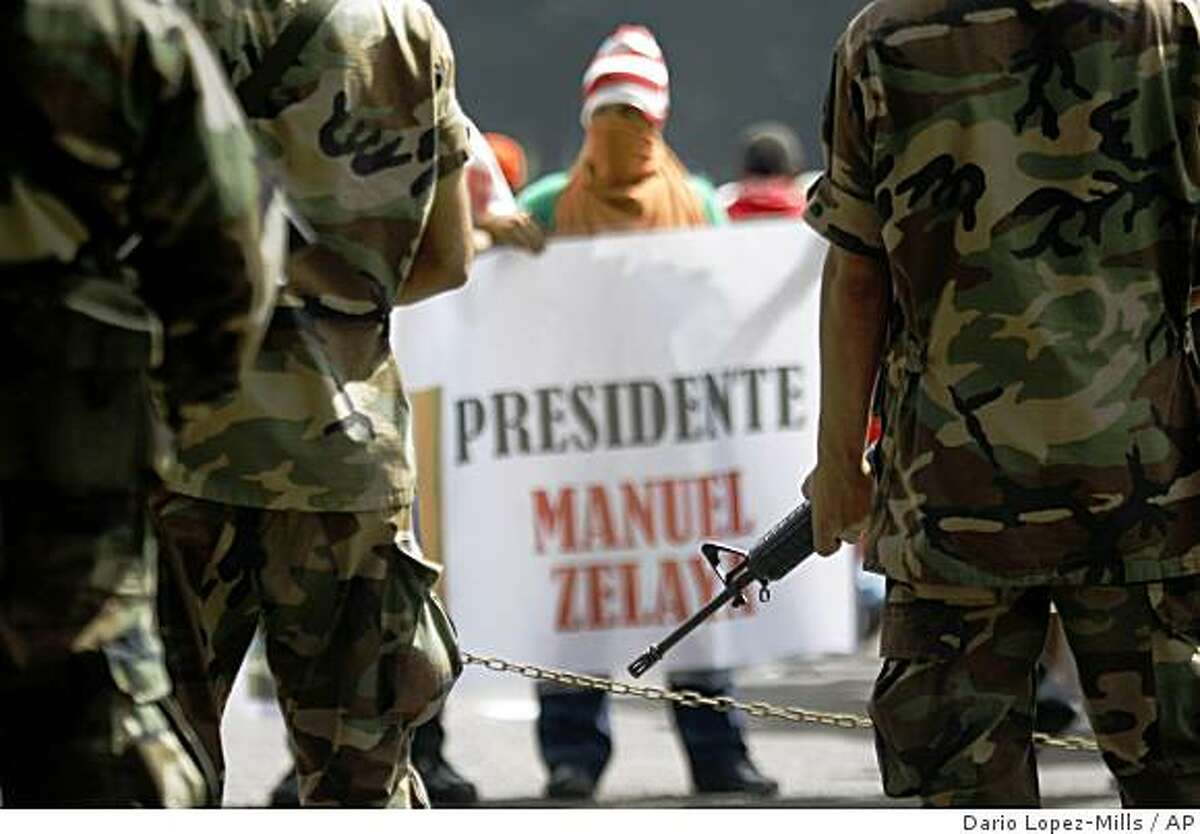 Supporters of Honduras' ousted President Manuel Zelaya stands in front of army soldiers during a protest in downtown Tegucigalpa, Thursday, July 2, 2009. The sign reads in Spanish