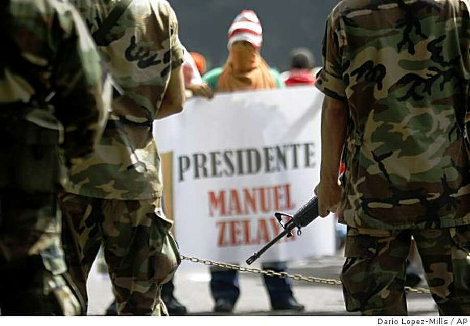 """Supporters of Honduras' ousted President Manuel Zelaya stands in front of army soldiers during a protest in downtown Tegucigalpa, Thursday, July 2, 2009. The sign reads in Spanish """"President Manuel Zelaya."""" (AP Photo/Dario Lopez-Mills) Photo: Dario Lopez-Mills, AP"""