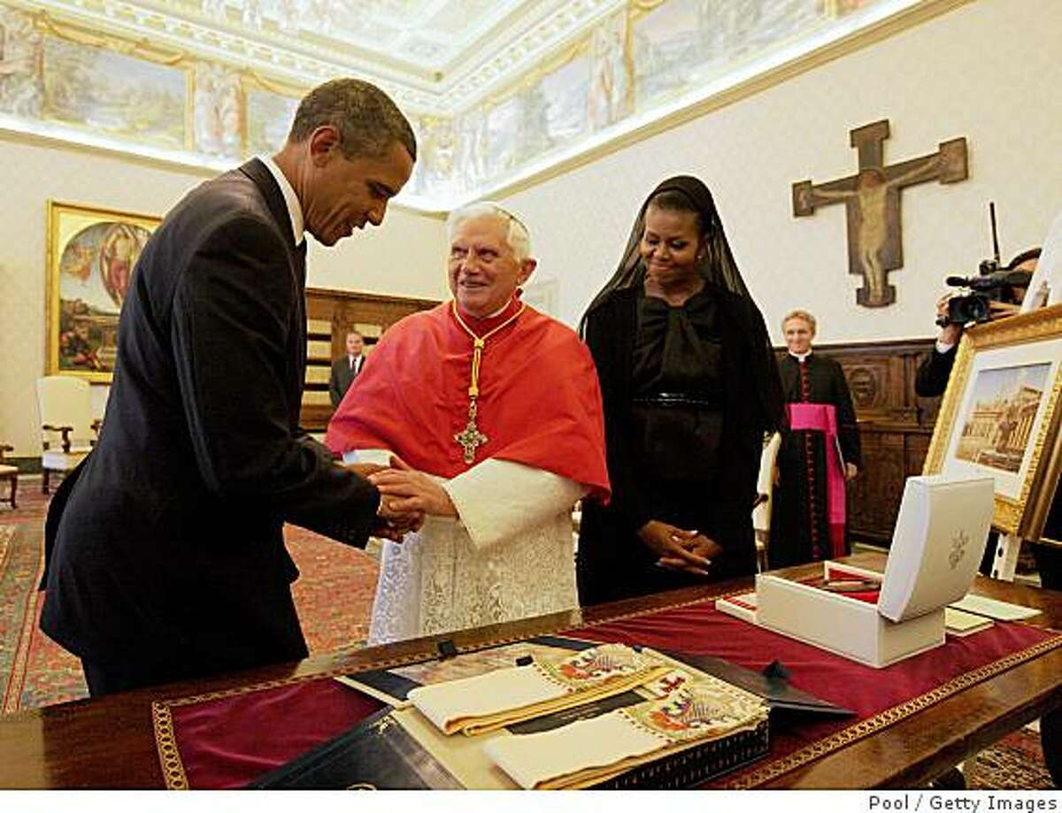 VATICAN CITY, VATICAN - JULY 10: US President Barack Obama (L) and First Lady Michelle Obama exchange gifts with Pope Benedict XVI in his library at the Vatican on July 10, 2009 in Vatican City, Vatican. Obama was meeting with The Pope for the first time as President following the G8 summit in L'Aquila, Italy. (Photo by Vatican Pool/Getty Images)