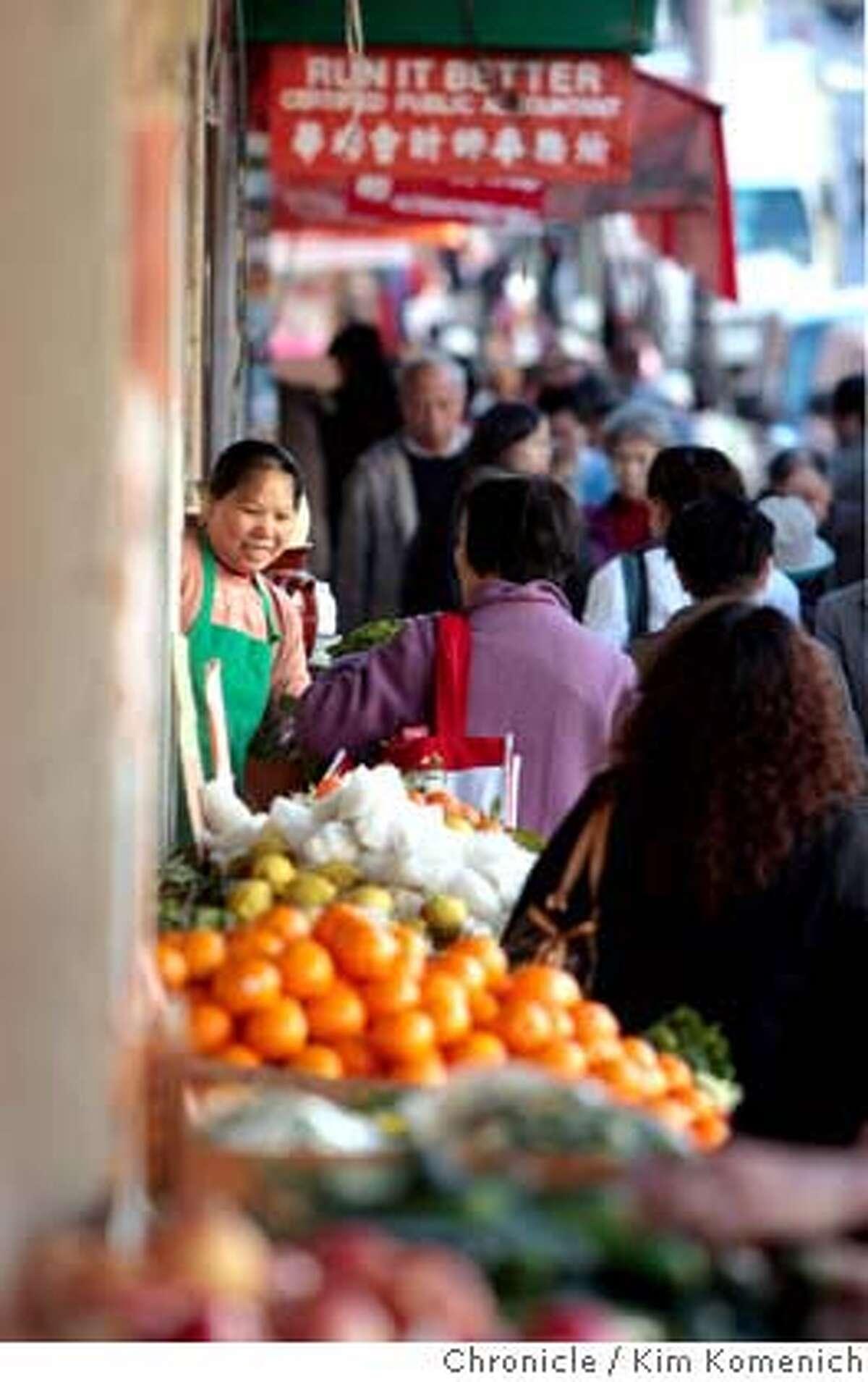 A merchant greets customers on Stockton Street near Washington Photo by Kim Komenich/San Francisco Chronicle