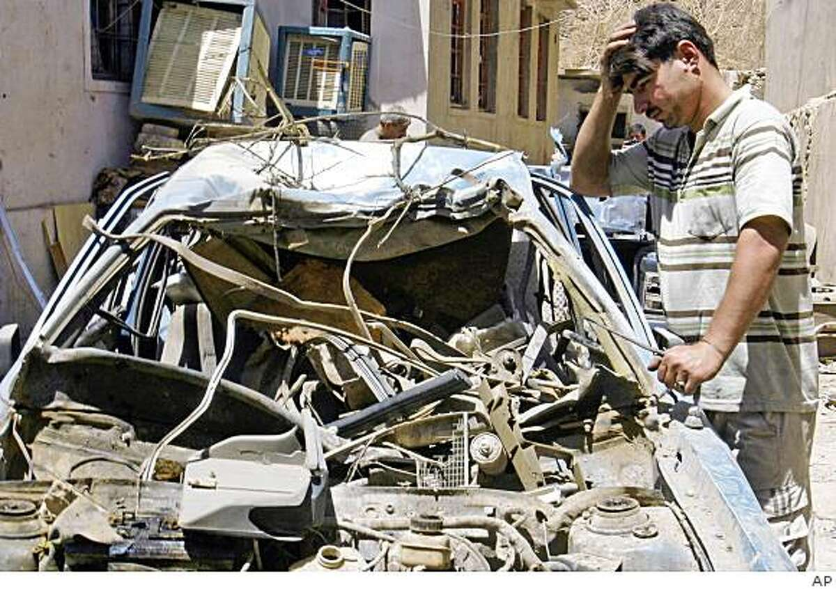 A man looks at a destroyed vehicle after a bombing near a Christian church and a mosque in Mosul, 360 kilometers (225 miles) northwest of Baghdad, Iraq, Monday, July 13, 2009. Iraqi authorities Monday imposed vehicle bans in two mostly Christian towns and increased security around churches in Baghdad after attacks targeting the Christian minority. Fearing car bombs, authorities on Monday imposed vehicle bans in the towns of Tilkaif and Hamdaniyah, predominantly Christian towns near the northern city of Mosul. (AP Photo)