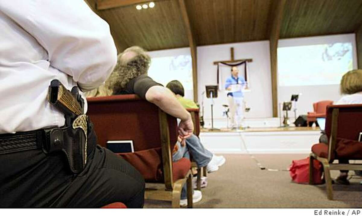 Cliff Meadows wears his firearm as he listens to pastor Ken Pagano during a service at the New Bethel Church where people were invited to bring their own firearms to the sanctuary in Louisville, Ky., Saturday, June 27, 2009.