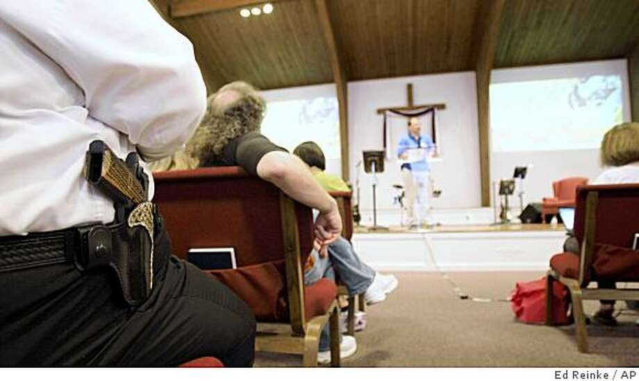 Cliff Meadows wears his firearm as he listens to pastor Ken Pagano during a service at the New Bethel Church where people were invited to bring their own firearms to the sanctuary in Louisville, Ky., Saturday, June 27, 2009. Photo: Ed Reinke, AP