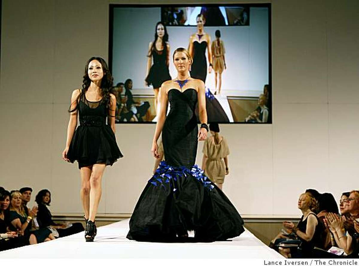 Student designer Coral Castillo walks side-by-side with a model wearing her black strapless evening gown with electric blue details on the skirt at the conclusion of the annual San Francisco Art Institute student fashion show held at the San Francisco design Center Saturday June 20, 2009.