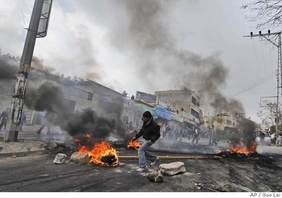 ###Live Caption:In this photo released by China's Xinhua News Agency, a Palestinian burns tyres to block the road during a rally against Israeli Defense Forces' military operation in Gaza Strip, in the West Bank town of Hebron, Monday, March 3, 2008. Israeli troops on Sunday shot and killed a Palestinian teenager during a violent demonstration in the West Bank against Israel's offensive in the Gaza Strip, Palestinian medical officials said. (AP Photo/Xinhua, Guo Lei)###Caption History:In this photo released by China's Xinhua News Agency, a Palestinian burns tyres to block the road during a rally against Israeli Defense Forces' military operation in Gaza Strip, in the West Bank town of Hebron, Monday, March 3, 2008. Israeli troops on Sunday shot and killed a Palestinian teenager during a violent demonstration in the West Bank against Israel's offensive in the Gaza Strip, Palestinian medical officials said. (AP Photo/Xinhua, Guo Lei)###Notes:###Special Instructions:THIS PHOTO RELEASED BY CHINA'S XINHUA NEWS AGENCY Photo: Guo Lei