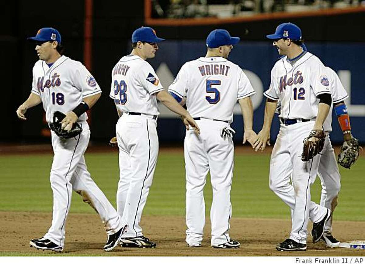 New York Mets' Jeff Francoeur (12) celebrates with teammates David Wright (5). Daniel Murphy (28), and Jeremy Reed (18) after their baseball game against the Cincinnati Reds Saturday, July 11, 2009, in New York. The Mets won the game 4-0. (AP Photo/Frank Franklin II)