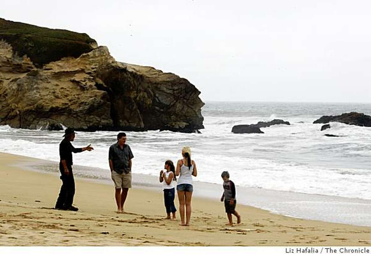 Longtime resident Blaise Francisco (left) warns the Kolomiyets family visting from Sacramento about the waves at Montara State Beach on Tuesday, June 30, 2009, where a mother and her daughter were swept out to sea and drowned yesterday in Montara, Calif.