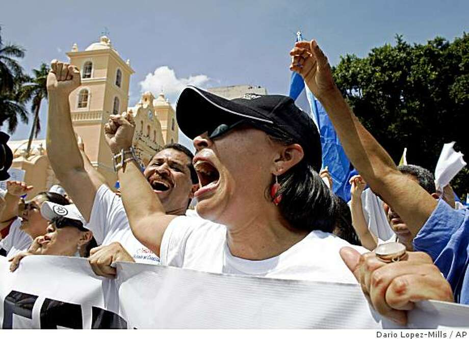 People against the return of ousted Honduran President Manuel Zelaya participate in a rally at the central park in Tegucigalpa, Tuesday June 30, 2009. Hondurans gather against the return of ousted Honduran President Manuel Zelaya during a rally at the central park in Tegucigalpa, Tuesday June 30, 2009.  The U.N. General Assembly on Tuesday unanimously condemned the military coup in Honduras and demanded President Manuel Zelaya's immediate return to power.(AP Photo/Dario Lopez-Mills) Photo: Dario Lopez-Mills, AP