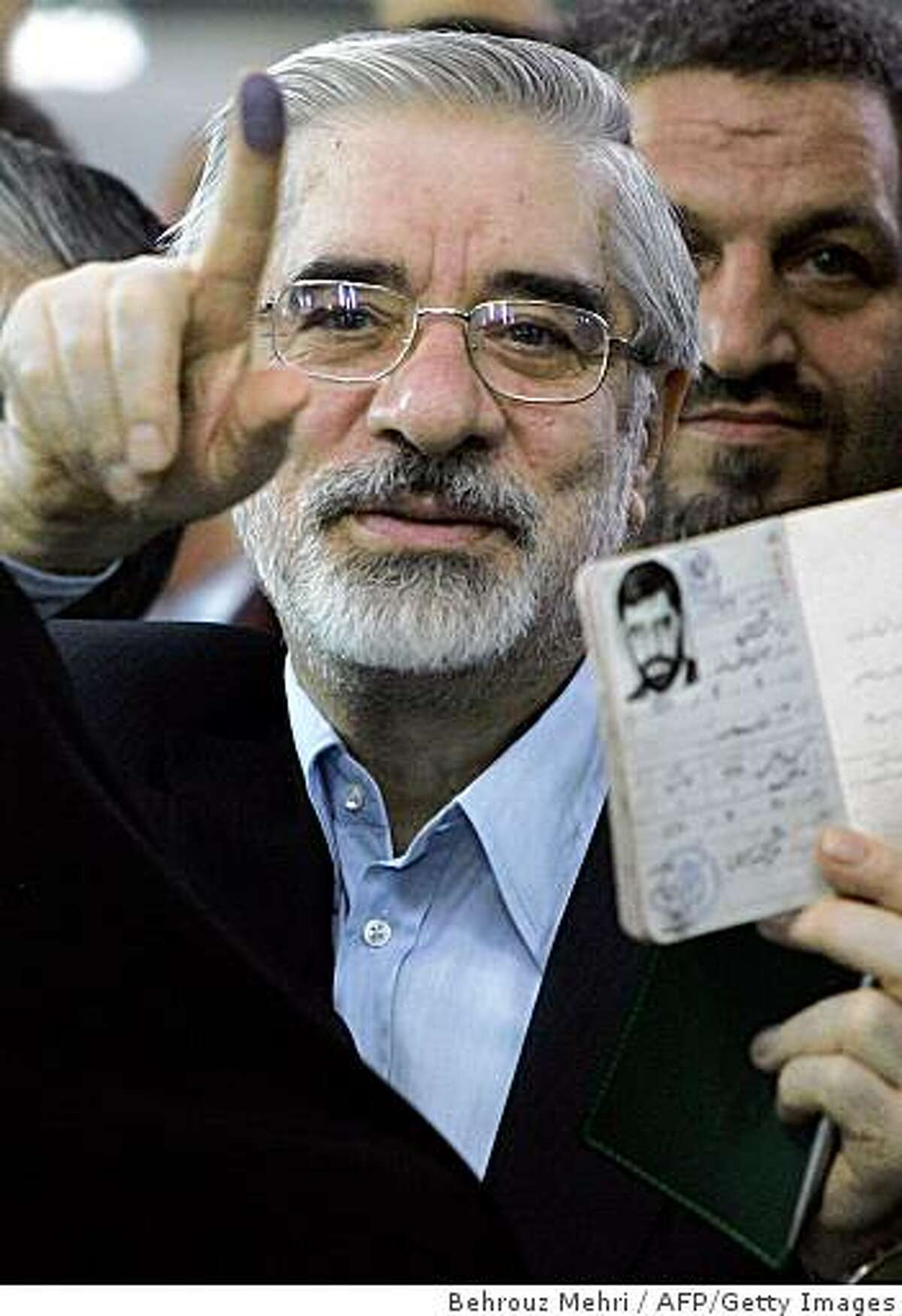 (FILES) Former Iranian Prime Minister and presidential candidate, Mir Hossein Mousavi, shows his certification card and ink-stained finger before voting at Ershad mosque in south of Tehran on June 12, 2009. Defeated Mousavi renewed his call on June 20 to cancel the result of last week's disputed election, his campaign website said. AFP PHOTO/BEHROUZ MEHRI (Photo credit should read BEHROUZ MEHRI/AFP/Getty Images)