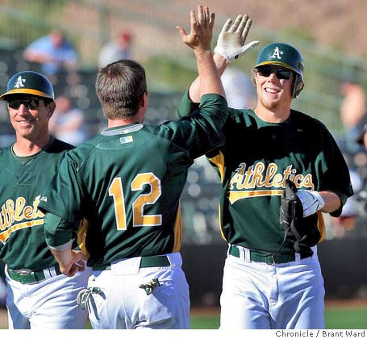 Aaron Cunningham is congratulated by 12 Donnie Murphy after his 9th inning hit scored the winning run Sunday. On March 2, 2008 the Oakland Athletics played the Colorado Rockies in a spring training exhibition game at Phoenix Municipal Stadium. Photo by Brant Ward / San Francisco Chronicle