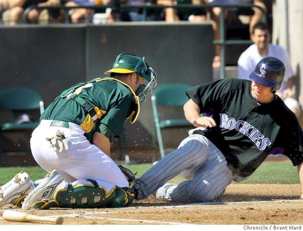 Garrett Atkins of Colorado was tagged out by A's catcher Rob Bowen in the first inning Sunday. On March 2, 2008 the Oakland Athletics played the Colorado Rockies in a spring training exhibition game at Phoenix Municipal Stadium. Photo by Brant Ward / San Francisco Chronicle Photo: Brant Ward