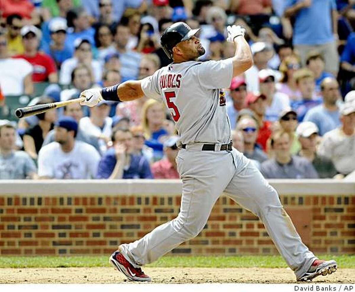St. Louis Cardinals' Albert Pujols hits a solo home run during the fifth inning of a baseball game against the Chicago Cubs, Friday, July 10, 2009, at Wrigley Field in Chicago. (AP Photo/David Banks)