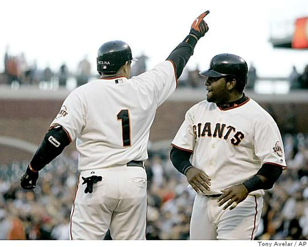 San Francisco Giants' Bengie Molina,left, points to the crowd after hitting a two-run home run against the San Diego Padres as Pablo Sandoval looks on in the first inning of a baseball game, Thursday, July 9, 2009, in San Francisco.