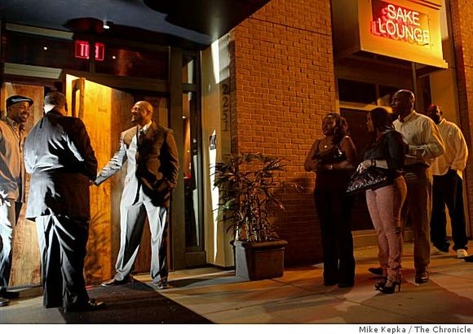 """This was a ghost town a year ago,"" said Merlin Edwards (2nd man from left) as he limits entry to a crowd of people trying to get into Ozumo, a new upscale sushi bar and lounge in the Broadway Grand complex on Friday June 5, 2009 in Oakland, Calif. Photo: Mike Kepka, The Chronicle"