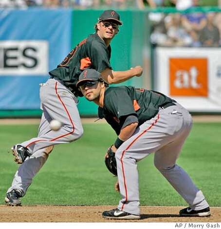 San Francisco Giants second baseman Travis Denker, right, watches the throw of shortstop Kevin Frandsen on a ball hit by Chicago Cubs' Kosuke Fukudome during the first inning at a baseball spring training game Sunday, March 2, 2008, in Mesa, Ariz. Fukudome beat the throw to first. (AP Photo/Morry Gash) Photo: Morry Gash