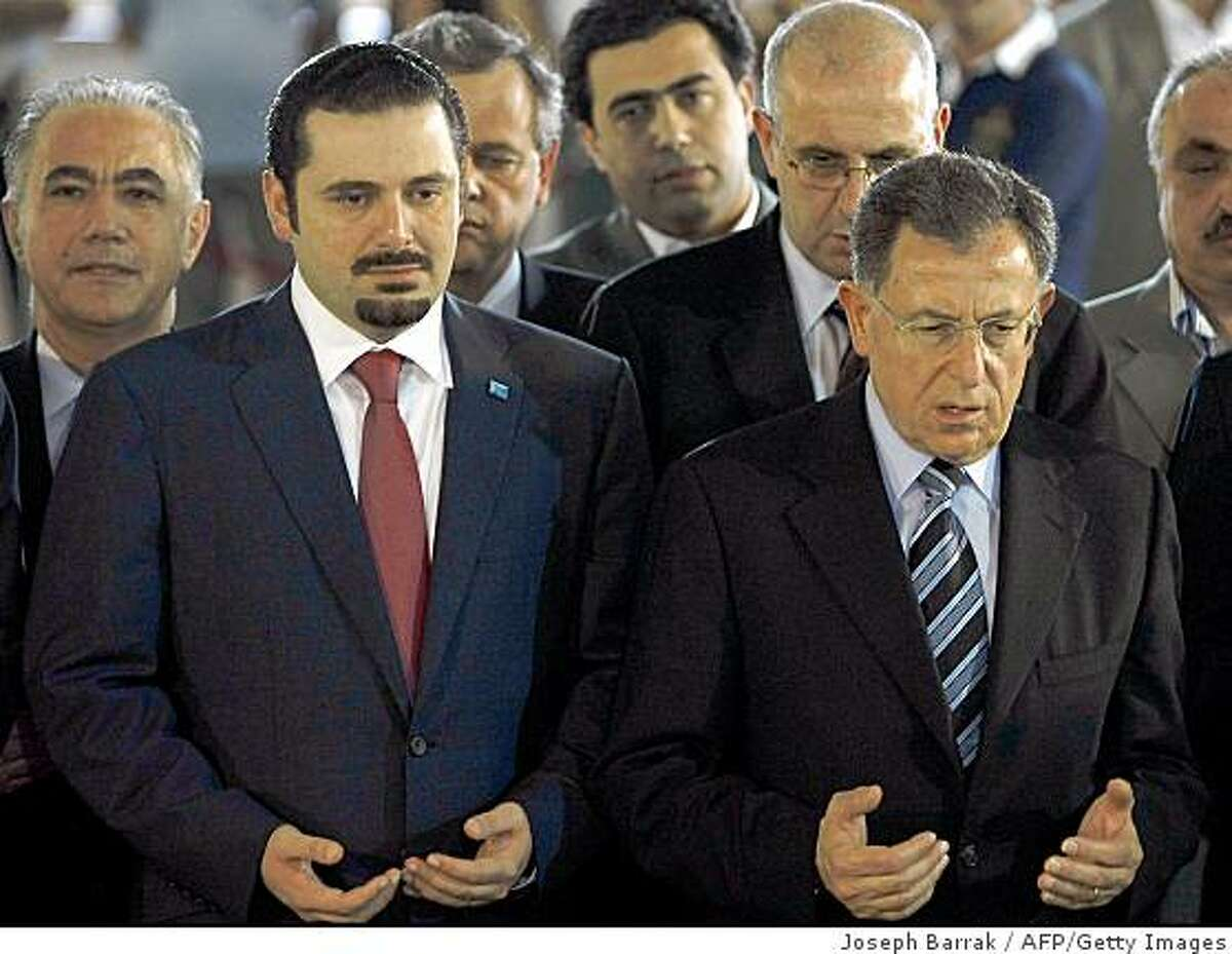 Outgoing Lebanese prime minister Fuad Siniora (R) and premier-designate Saad Hariri pray over the tomb of the latter's father, slain former prime minister Rafiq Hariri, in Beirut on June 27, 2009. Hariri, who was propelled into the heart of Lebanese politics following the assassination of his father four years ago, was himself named to the top job on June 27. AFP PHOTO/JOSEPH BARRAK (Photo credit should read JOSEPH BARRAK/AFP/Getty Images)